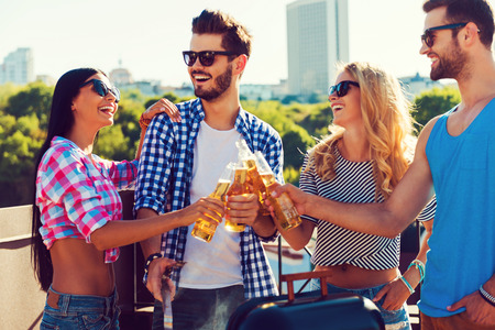 barbecuing: Party on! Group of happy young people clinking glasses with beer and barbecuing while standing on the roof