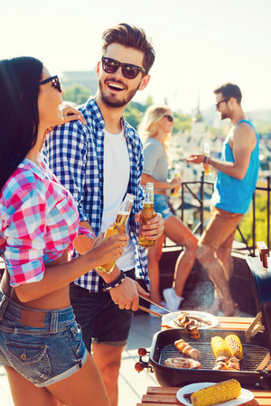 barbecuing: Perfect day for barbecue. Cheerful young couple barbecuing and holding bottles with beer while two people talking to each other in the background