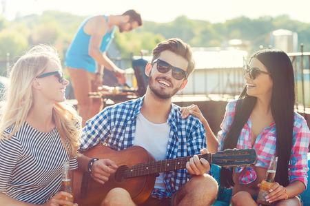 Compartilhando bom tempo. Três jovens alegres que lig um com o outro e sentam-se no saco de feijão com guitarra enquanto o homem churrasco em segundo plano