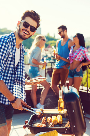 bbq background: Tasty food and good company. Happy young man barbecuing and looking at camera while three people having fun in the background