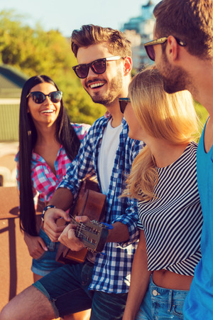 group of young adults: Enjoying time together. Side view of four young people bonding to each other and looking at camera while standing on the roofwith guitar
