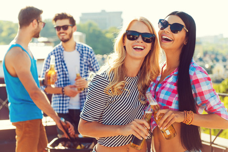 Having great time together. Two cheerful young women clinking glasses with beer and smiling while two men barbecuing in the background