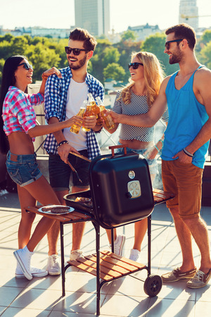 barbecuing: Cheers to friends! Full length of fourjoyful young people clinking glasses with beer and barbecuing while standing on the roof Stock Photo