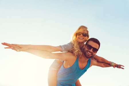 people: 高飛揚的浪漫。面帶微笑的年輕男子捎帶他的女朋友,同時保持張開雙臂低視角 版權商用圖片