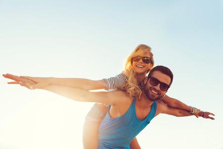 happiness: Alto el romance de vuelo. Ángulo de visión baja del hombre joven sonriente que lleva a cuestas a su novia mientras extendidos manteniendo los brazos