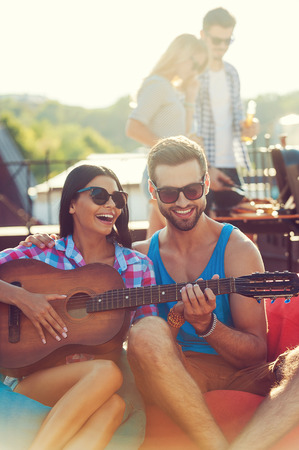 heterosexual couple: Guitar fun. Joyful young man teaching his girlfriend to play the guitar while two people barbecuing in the background