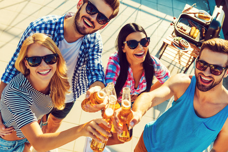 looking to camera: Celebrating their friendship. Top view of four cheerful young people clinking glasses with beer and looking at camera while standing outdoors Stock Photo