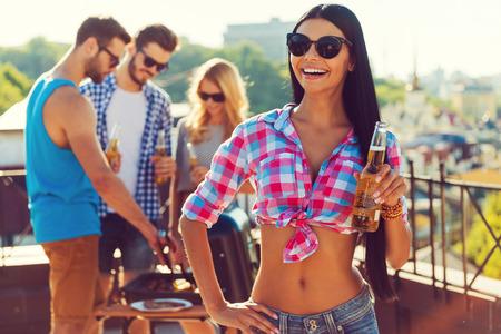 hombre tomando cerveza: Chill tiempo con amigos. Mujer joven feliz celebraci�n de una botella de cerveza y sonriendo mientras tres personas barbacoa en el fondo Foto de archivo
