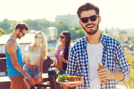 Buena comida con los mejores amigos. Hombre joven sonriente que sostiene la botella de cerveza y un plato con comida, mientras que tres personas barbacoa en el fondo Foto de archivo