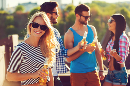 chilling out: Chilling out with friends. Smiling young woman holding bottle of beer and looking at camera while three people talking to each other in the background