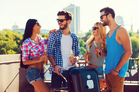 barbecuing: Joyful time with friends. Group of cheerful young people holding bottles with beer and barbecuing while standing on the roof