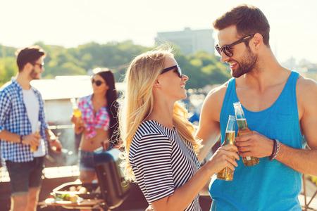 hombre tomando cerveza: Saludos a nosotros! Smiling vasos tintinean de los pares con la cerveza y mirando el uno al otro, mientras que dos personas barbacoas en el fondo