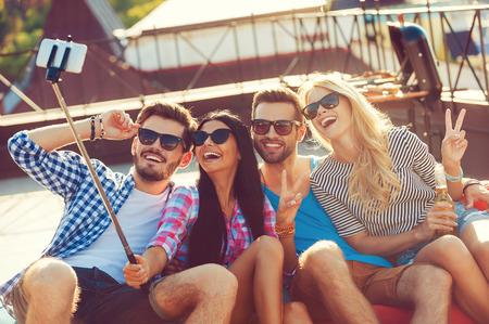 amicizia: Catturare il momento. Vista dall'alto di quattro giovani allegri legame tra loro e rendendo selfie su smart phone, mentre seduto sul tetto