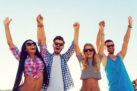 grupo de hombres: Disfrutar de tiempo libre de preocupaciones. Ángulo de visión baja de cuatro jóvenes alegres que llevan a cabo las manos y mantener los brazos en alto mientras está de pie contra el cielo