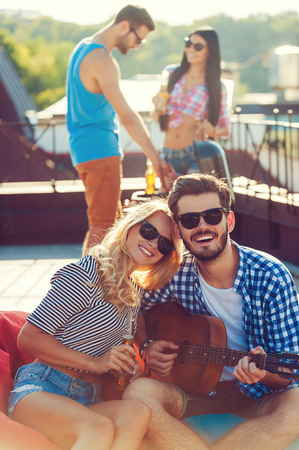 bean bag: Enjoying time with friends. Beautiful young couple bonding to each other and sitting on the bean bag with guitar while two people barbecuing in the background