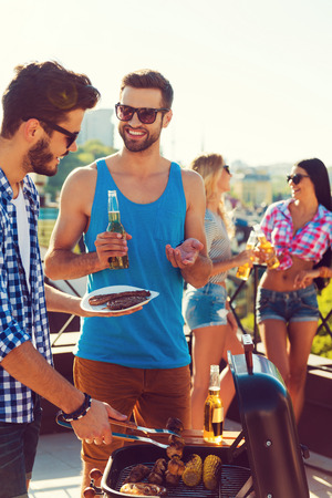 barbecuing: Perfect summer lunch. Two cheerful young men barbecuing and smiling while two women talking to each other in the background