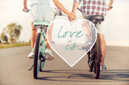 two hands: Love is... Rear view of young couple holding hands while riding on bicycles along the road
