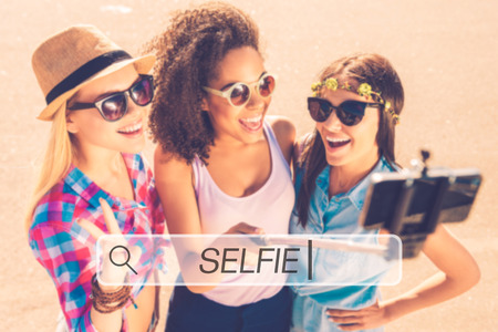 group search: Selfie time! Top view of three young happy women making selfie by their smart phone while standing outdoors together Stock Photo