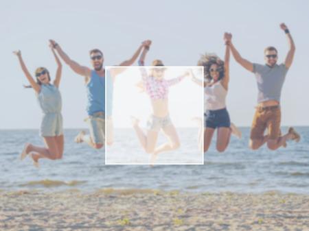 personas saltando: Diversion con amigos. Grupo de jóvenes felices tomados de la mano y saltando con mar de fondo