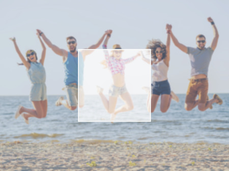 multilayered: Fun with friends. Group of happy young people holding hands and jumping with sea in the background