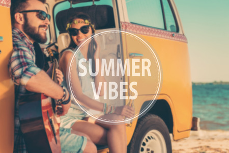 minivan: Summer vibes. Happy young couple enjoying time together while sitting in their retro minivan with sea in the background