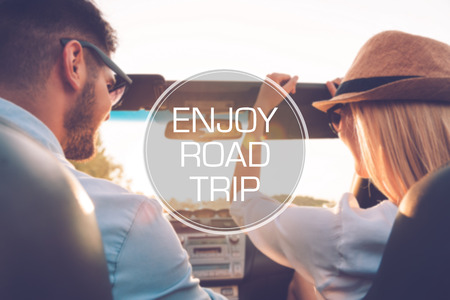 multilayered: Enjoy roadtrip. Rear view of joyful young couple having fun while riding in their convertible Stock Photo