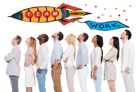 teamwork people: Teamwork is a key to success. Side view of positive diverse group of people in smart casual wear looking up while standing in a row and against white background