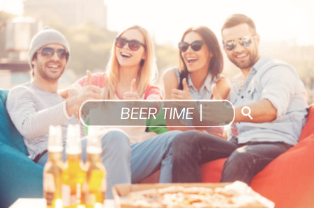 sitting people: Beer time. Four young cheerful people showing their thumbs up and smiling while sitting on bean bags at the outdoors terrace with pizza and beer laying on foreground
