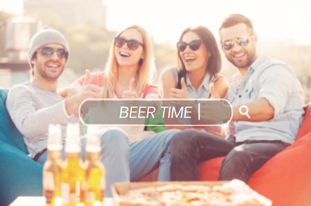 gente sentada: Tiempo de la cerveza. Cuatro personas alegres jóvenes que muestran sus pulgares hacia arriba y sonriendo mientras está sentado en bolsas de frijol en la terraza al aire libre con la pizza y la cerveza que pone en primer plano Foto de archivo