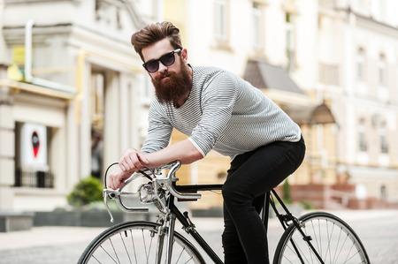 시간은 길을 칠합니다. 야외 그의 자전거에 앉아있는 동안 잘 생긴 젊은 수염 남자가 카메라를보고