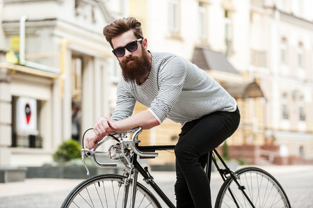 Time to hit the road. Handsome young bearded man looking at camera while sitting on his bicycle outdoors