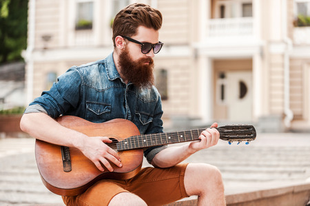 street musician: Street musician. Handsome young bearded man playing the guitar while sitting outdoors