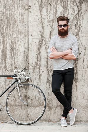 beau mec: Charme beau. longueur totale d'un jeune homme en gardant les bras crois�s et barbus regardant la cam�ra tout en se tenant pr�s de sa bicyclette contre le mur de b�ton Banque d'images