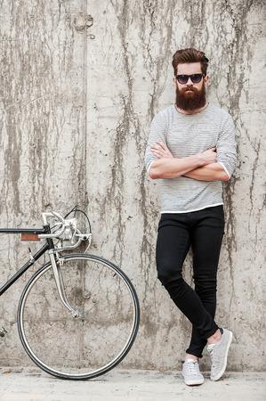 Charming knap. Volledige lengte van de jonge bebaarde man houden gekruiste armen en kijken naar de camera terwijl je in de buurt van zijn fiets tegen de betonnen muur