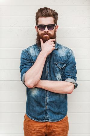 estilo urbano: Fresco y confiado. hombre barbudo joven con estilo que mira la c�mara y de la mano en la barbilla mientras est� de pie al aire libre