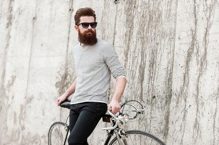 ストリート スタイル。物思いにふける若者を生やした彼の自転車で傾いているとコンクリートの壁に立っている間よそ見