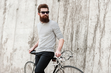 life style: Street style. Pensive young bearded man leaning at his bicycle and looking away while standing against the concrete wall