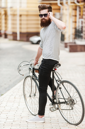cool man: Confident and stylish. Full length of confident young bearded man adjusting eyewear and looking at camera while sitting on his bicycle outdoors