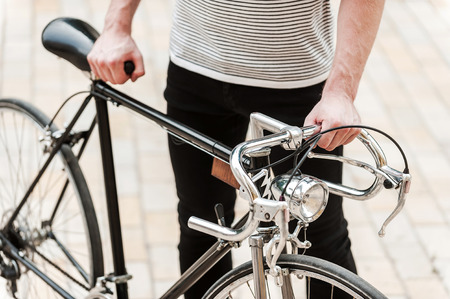 This bike is my pride. Close-up of young man holding hands on his bicycle while standing outdoors