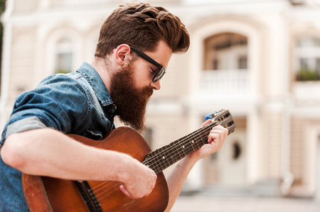 Intense guitar player. Young bearded man playing the guitar while sitting outdoors