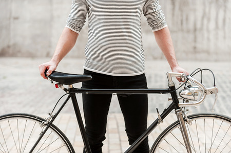 Proud of his bike. Close-up of young man holding hands on his bicycle while standing outdoors