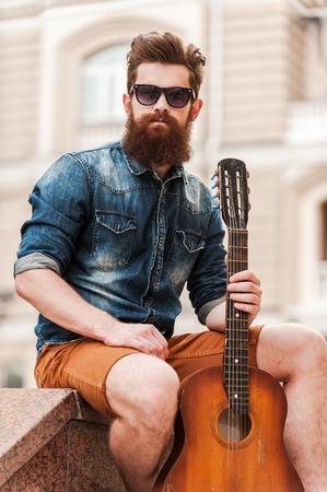 hairstyle: Music is my life. Confident young bearded man holding guitar and looking at camera while sitting outdoors