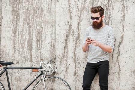 стиль жизни: Охлаждающая после хорошей езды. Красивый молодой бородатый человек держит мобильный телефон, стоя рядом с его велосипедом против бетонной стены Фото со стока