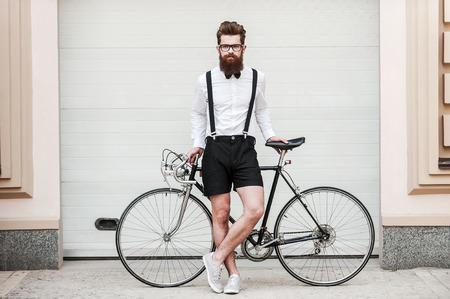 乗車のための準備はできましたか若いハンサムな髭の男彼の自転車で傾いていると屋外で立ってながらカメラ目線の全長