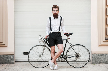 Are you ready for ride? Full length of handsome young bearded man leaning at his bicycle and looking at camera while standing outdoors