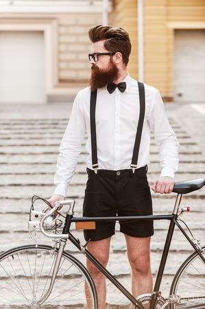 Man n stijl. Zekere jonge bebaarde man met de handen op zijn fiets en wegkijken, terwijl die zich in openlucht