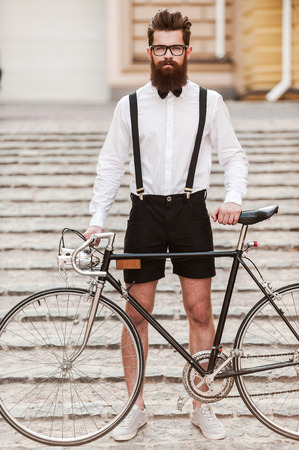 cool man: My bike is essential to my style. Full length of handsome young bearded man holding hands on his bicycle and looking at camera while standing outdoors Stock Photo