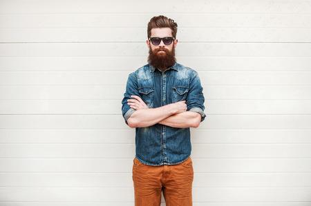 髭とスタイリッシュです。自信を持って若いあごひげを生やしたカメラ目線と屋外に立っている間交差腕を維持します。