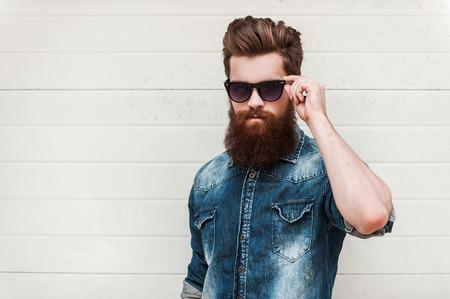 confianza: Robusta y varonil. Hombre barbudo joven confidente que mira la cámara y el ajuste de las gafas mientras está de pie al aire libre