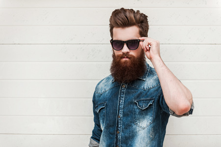 pensive man: Rugged and manly. Confident young bearded man looking at camera and adjusting eyewear while standing outdoors